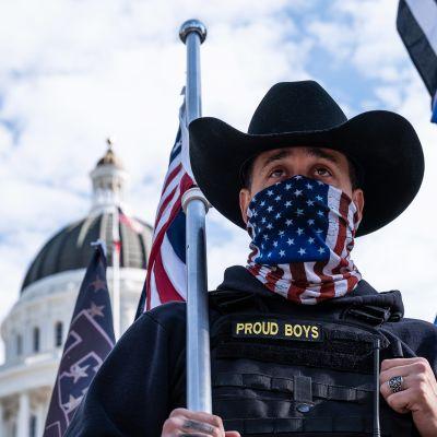 Äärioikeistolaisen Proud Boys ryhmän jäsen Amerikan lippu kädessä.