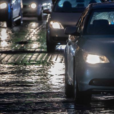Autoilijoita illan hämärässä vesisateessa..