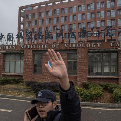 Vartija yrittää estää valokuvaajaa ottamasta kuvia Wuhanin virologian instituutin edessä.