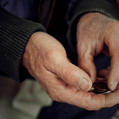 Vanhemmalla henkilöllä on kolikoita kädessä.