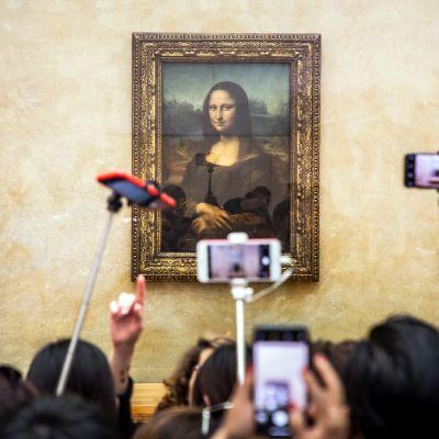 Museovieraat valokuvaavat naista esittävää öljyvärimaalausta Louvressa.
