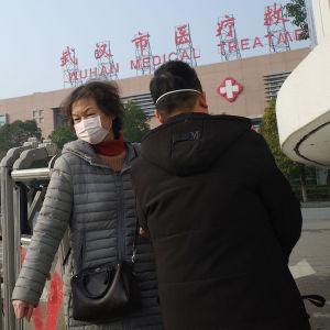 En kvinna och en man med munskydd utanför en hälsovårdscentral i Wuhan, Kina.