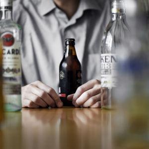 Mies istuu pöydän ääressä, joka on täynnä alkoholipulloja.