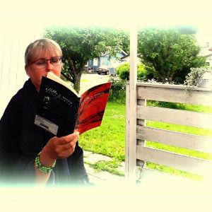 Kaikki kirjasta kirjabloggaaja lukemassa kesäisellä terassilla Anni Sumarin teosta Mitta ja Määrä