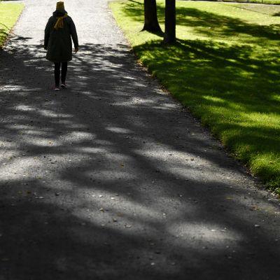 Nainen kävelee puistikossa.