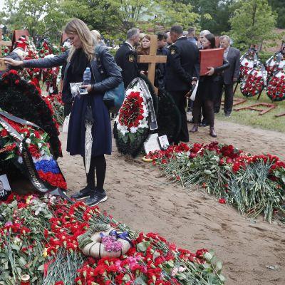 Sureva nainen koskettaa kädellään hautaristiä. Taustalla muita surijoita.
