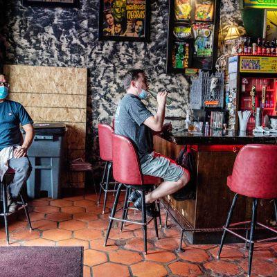 Kasvosuojaimiin pukeutuneet miehet istuvat vaarissa Teksasin Austinissa.