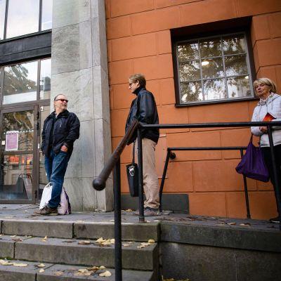Ihmisiä kirjaston edessä.