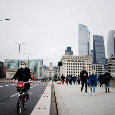 Henkilö pyöräilee kasvomaski kasvoillaan London Bridgen yli.