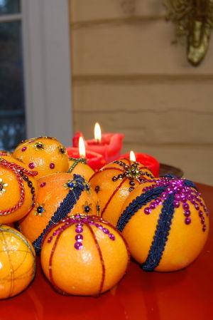Eb röd bricka med mandariner och apelsiner som dekorerats med paljetter och sidenband i olika färger.