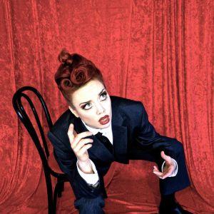Burleskartist sitte rpå en stor med målade läppar och rött hår