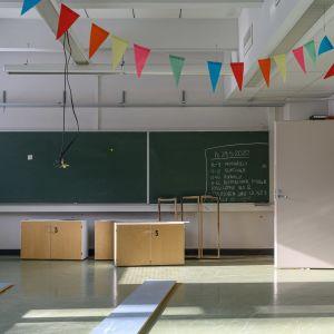 Urpolan koulun tyhjä luokka. Katossa on värikäs viiri.