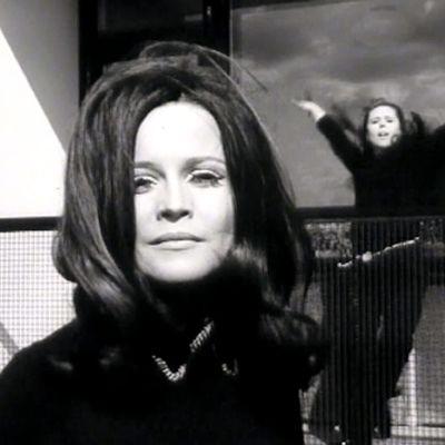 Laulaja Carola etualalla, takana pop-tanssijatar tanssii mustissa vaatteissa parvekkeella.