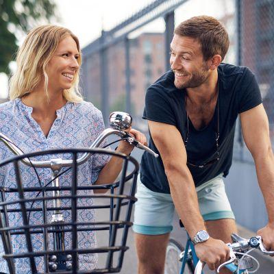 Naine ja mies pyörien kanssa keskustelevat tiellä.
