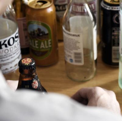 En man sitter vid ett bord fullt av alkoholflaskor.