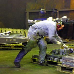 Nedre kroppen av person i overall lyfter metallföremål på fabriksgolv.