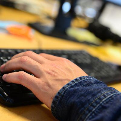 Miehen kädet tietokoneen näppäimistöllä.