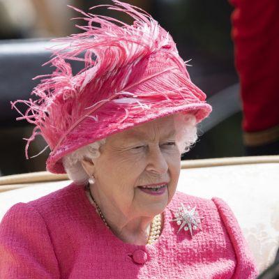 Kuningatar Elisabet vaaleanpunaisessa, sulin koristellussa hatussa.