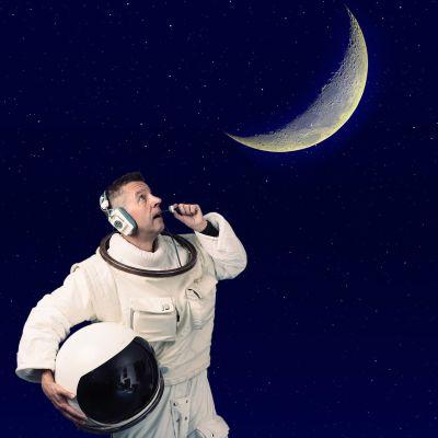 Jari Mäkinen avaruuspuvussa, taustalla Kuu