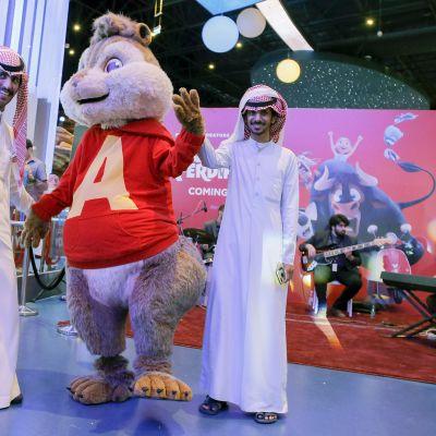 Saudimiehet poseeraavat elokuvamaskottien kanssa.