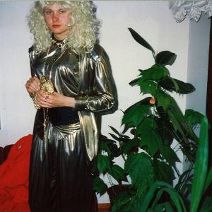 Harri Henttinen pukeutuneena naisten kultaiseen haalariin ja vaaleaan peruukkiin.