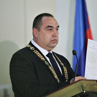 Plotnitski seisoo esittelee asiakirjaa tummassa puvussa kultakäädyt kaulassaan. Edessä on puhujanpönttö ja taustalla näkyy lippuja.