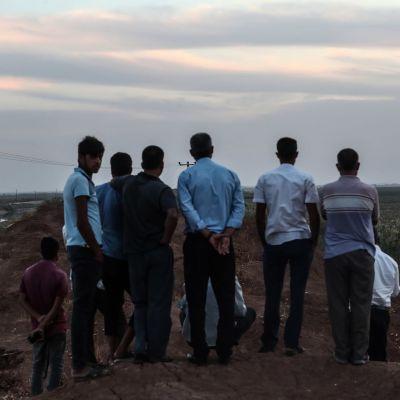 Miehet katsovat Turkin puolelta rajaa, kun Syyrian puolella Tel Abyadin kaupungissa savuaa iskujen jäljiltä.