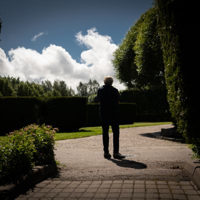 Nainen seisoo puistokäytävällä