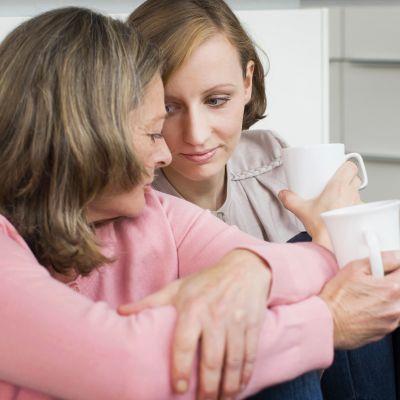 äiti ja tytär keskustelee kahvikupit kädessä