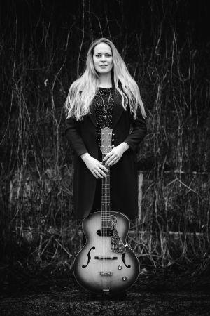 Kvinna med långt ljust hår ser mot kameran och ler. Hon håller i en gitarr.