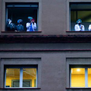 Sjukvårdspersonal står i två sjukhusfönster med anisktsmasker och tar del i den nya traditionen att applådera åt sjukvårdspersonal klockan 8 på kvällen.