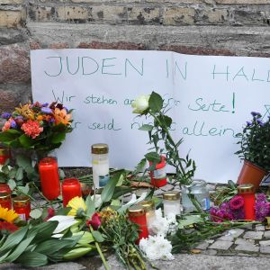 """Maassa on kukkia ja kynttilöitä, sekä saksankielinen lappu, jossa lukee """"Hallen juutalaiset, olemme rinnallanne, ette ole yksin"""""""