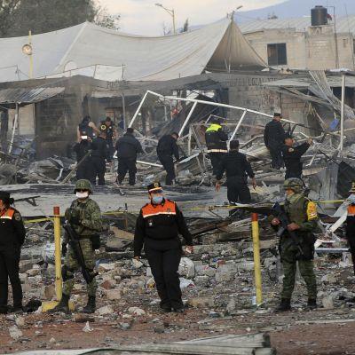 Pelastustyöntekijöitä raunioituneella ja hiiltyneellä torilla.