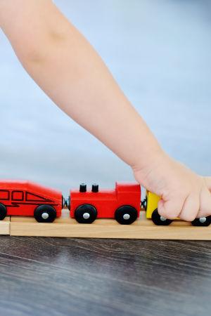 Barn som leker med leksak, ett tåg och tågvagnar gjorda i trä.