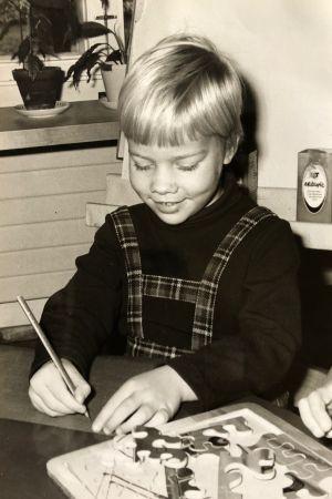 Anna-Maja Henriksson som barn. Hon sitter och skriver vid ett bord.