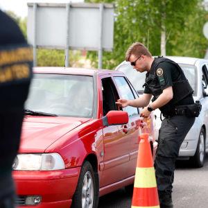 En gränsövervakare talar med en person som sitter i en röd bil.