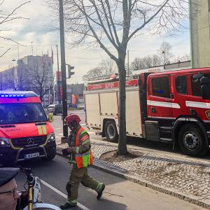En ambulans och en brandbil på en gata. Räddningspersonal går mellan bilarna och nyfikna förbipasserare står intill.