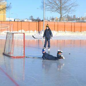 Två barn spelar ishockey, det ena har ramlat och ligger på mage