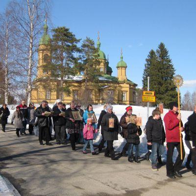 Ihmisiä kävelee jonossa ristisaatossa kantaen ikoneita.