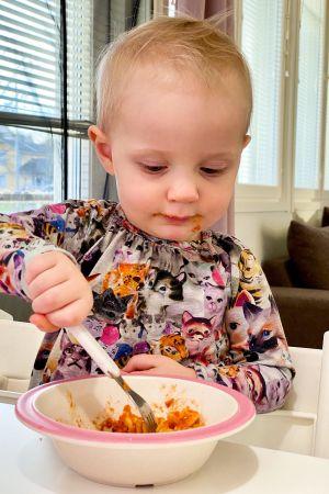 en ettåring äter mat med gaffel