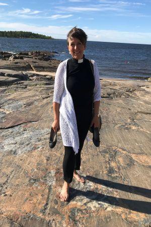 Prästen Patrica Strömbäck med skorna i handen på en klippa vid havet i Pörkenäs.