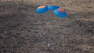 Blue Originin kapseli laskeutuu maahan lentonsa jälkeen kolmen laskuvarjon varassa.