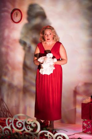 Sari Puumalaisen näyttelemä Emine punaisessa mekossa, pitää sylissään ruttuista hääyönä tahriintunutta lakanaa.