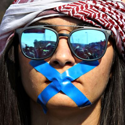 Irakilainen mielenosoittaja on laittanut teipin x-kirjaimen muotoon suunsa eteen Bagdadissa 5. helmikuuta.