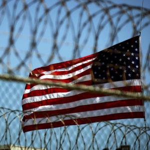 En amerikansk flagga bakom taggtråd som omger fånglägret Guantanamo Bay
