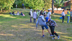 I bakgrunden sitter några människor på filtar på marken och har picknick. Till höger fram i bild leker två pojkar och bakom dem syns mera folk som står och umgås.