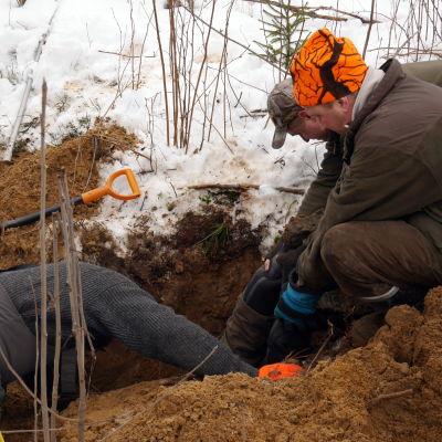 Metsästäjä on pää edellä kuopassa katsomassa näkyykö supikoiria.