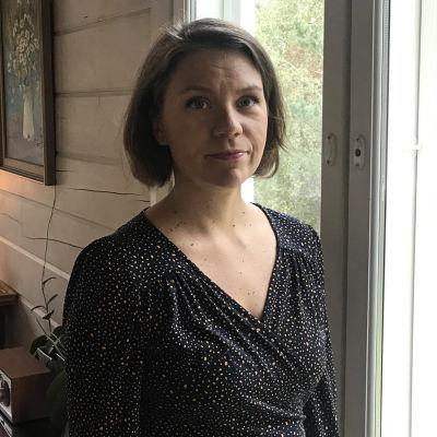 Anna Rajamäki seisoo ikkunan edessä