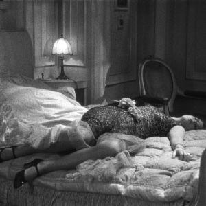 Murhattu nainen makaa vuoteella. Kuva elokuvasta Laukaus äänifilmistudiolla
