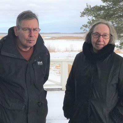 En man och en kvinna står på en snötäckt strand.